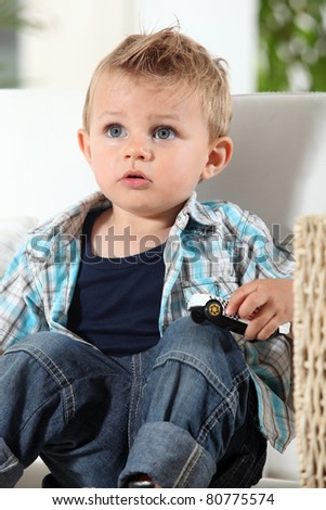 Little boy watching television with a toy car - stock photo