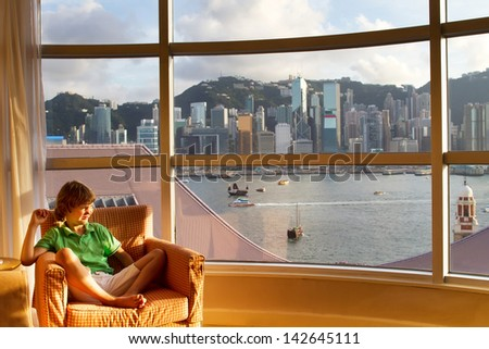 Little boy watching the view of the Hong Kong bay out of a hotel - stock photo