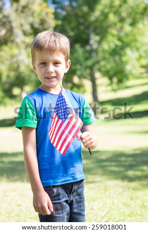 Little boy waving american flag on a sunny day - stock photo