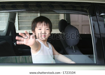 Little boy waving in the car - stock photo
