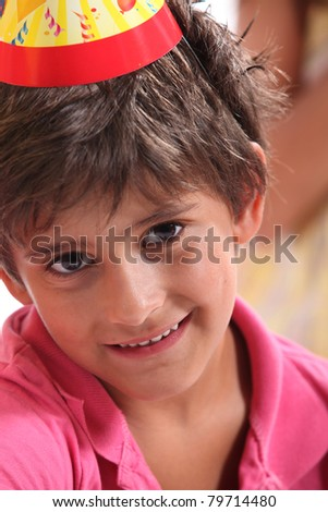 Little boy wearing a birthday party hat - stock photo