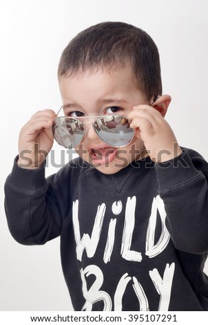 little boy wearing a black sweaty with wild boy written on it taking off sun glasses with a funny angry face isolated on white