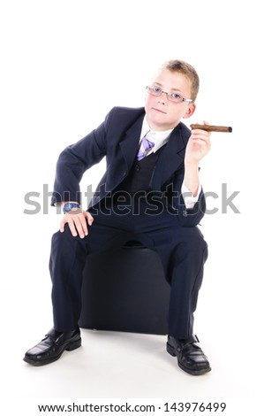 Little boy wearing a dark suit and tie and sitting on a black seat he holds a big cigar in his hand and looks confidently into the camera.