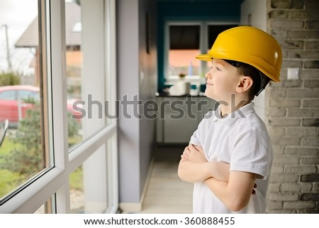 Little boy wearing a engineering helmet and looking throught window. Arms crossed on chest - stock photo