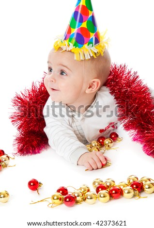 Little boy wearing a Santa hat and playing with baubles. Isolated on white background