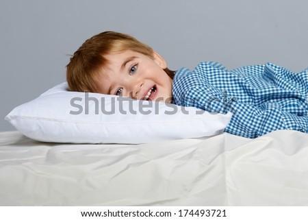 Little boy wearing blue pyjamas in bed - stock photo