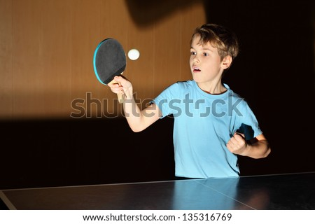 little boy wearing blue shirt playing ping pong; concentrated face - stock photo