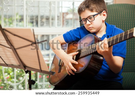 Little boy wearing glasses and learning a new guitar song from a sheet music - stock photo