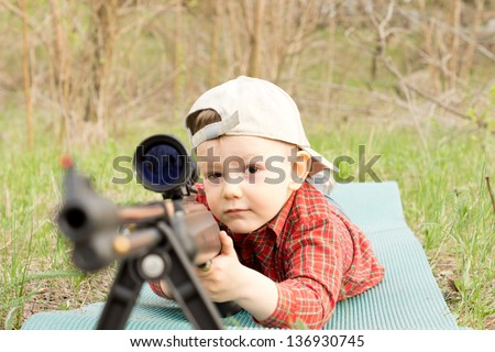 Little boy wearing hat plays with shotgun outdoors - stock photo