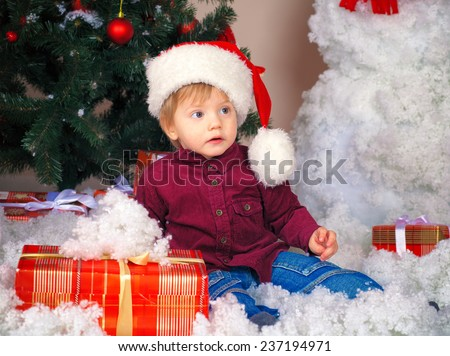 Little boy wearing Santa hat with Christmas present near decorated fir tree - stock photo