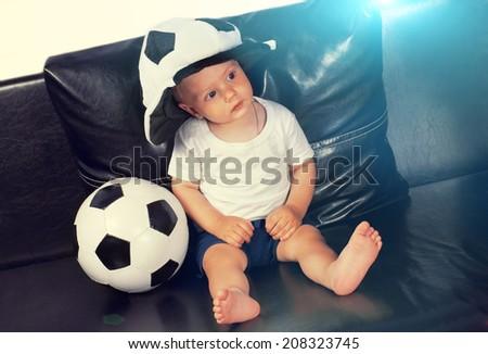 Little boy wearing soccer fan's hat with football - stock photo