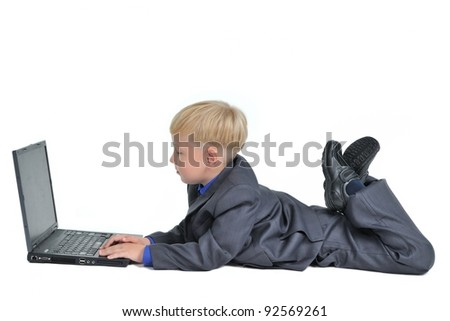 Little boy wearing suit working on laptop, isolated on white background - stock photo