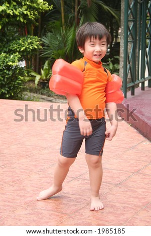 Little boy wearing swimming costume, standing bare-footed - stock photo