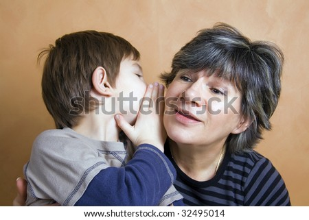 Little boy whispering a secret to his grandmother - stock photo