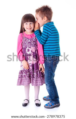 Little boy whispering interesting story into girlfriend's ear