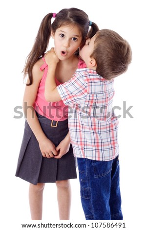 Little boy whispering something to surprised girl, isolated on white - stock photo