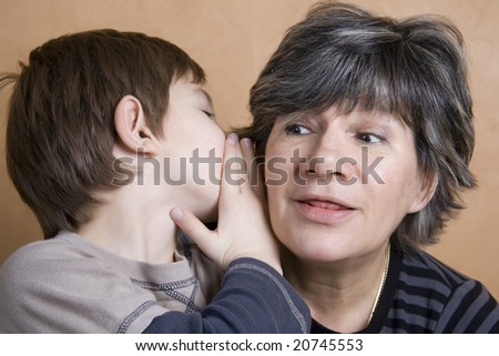Little boy whispering to his grandmother - stock photo