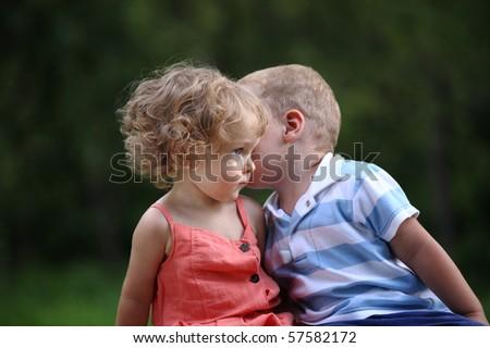 Little boy whispers to lovely girl in ear - stock photo