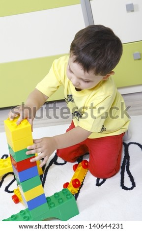 Little boy who builds castles with plastic cubes