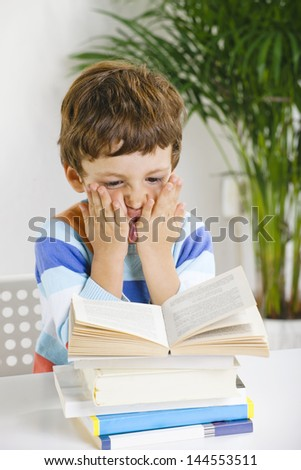 Little boy with a books./ 	Stressed schoolboy studying in home. - stock photo
