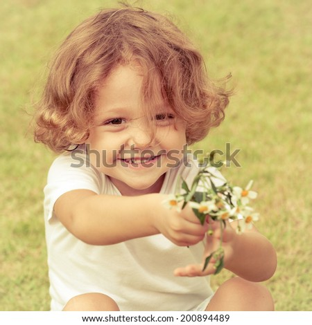 little boy with a bouquet of daisies sitting on the grass at day time - stock photo