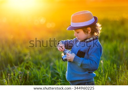 Little boy with a camera outdoors