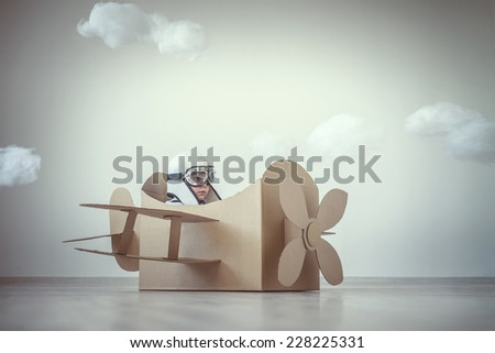 Little boy with a cardboard airplane indoors - stock photo