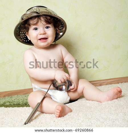 little boy with a colander on his head with a ladle in his hand - stock photo