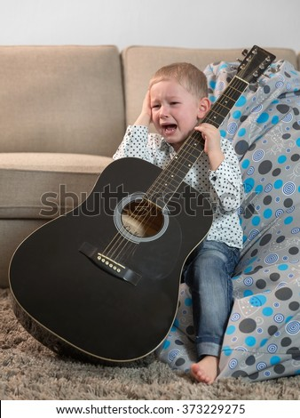 Little boy with a guitar and crying - stock photo