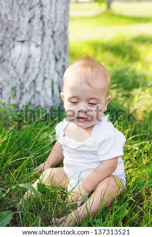 Little boy with a happy kind sits on a grass