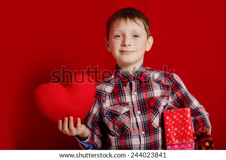 little boy with a heart of toy and gift box in hands - stock photo