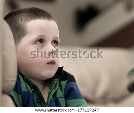 little boy with a look of fear upon his face - stock photo