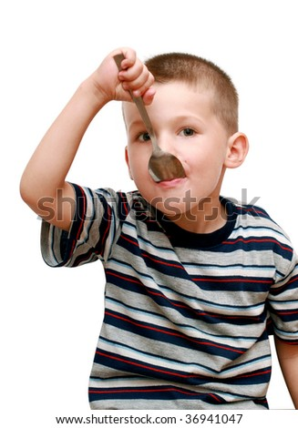 little boy with a spoon in mouth - stock photo