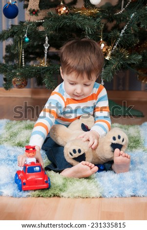 Little boy with a teddy bear and a machine at the Christmas tree (3 years old) - stock photo