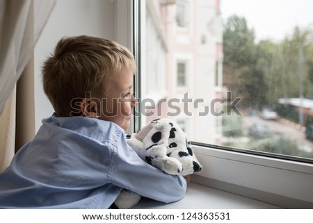 little boy with a toy near a window - stock photo