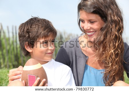 little boy with American football sat with mother - stock photo