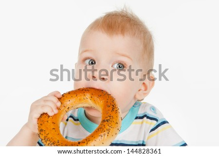 Little boy with bagel, on a gray background - stock photo