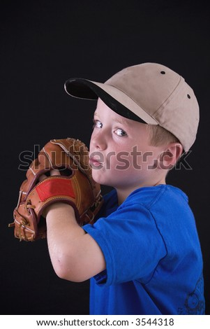 Little boy with baseball cap and glove ready to pitch the ball. - stock photo