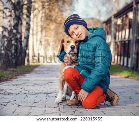 Little boy with beagle on the autumn street - stock photo