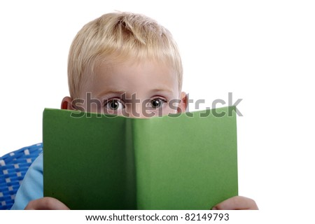 little boy with big eyes looking from over a book. isolated on white background - stock photo
