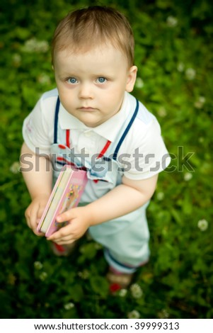 Little boy with book in hands - stock photo