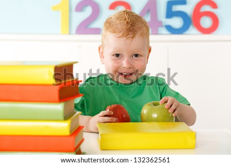 little boy with books and apple - stock photo