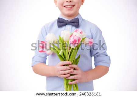 Little boy with bunch of fresh tulips - stock photo