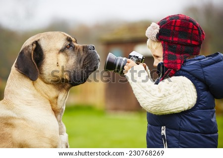 Little boy with camera is shooting his dog - stock photo