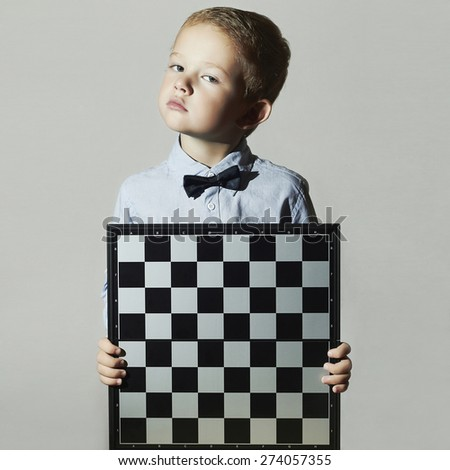 Little boy with chessboard.Bow-tie.Little genius Child. Intelligent game - stock photo