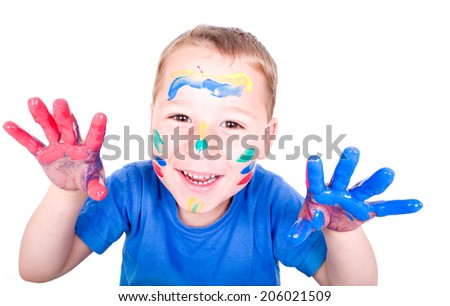 little boy with colored fingers laughs into the camera