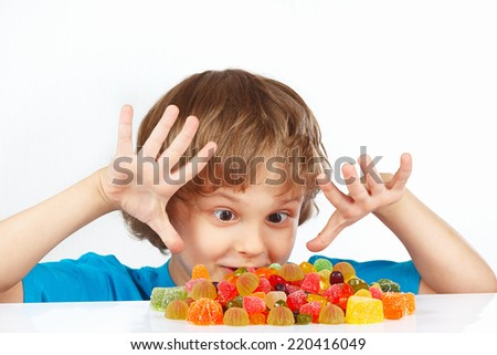 Little boy with colored jelly candies on a white background - stock photo
