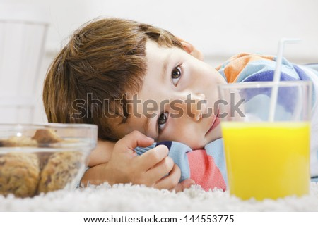 Little boy with cookies and orange juice stretching on carpet./ Closeup of child with breakfast in home. - stock photo