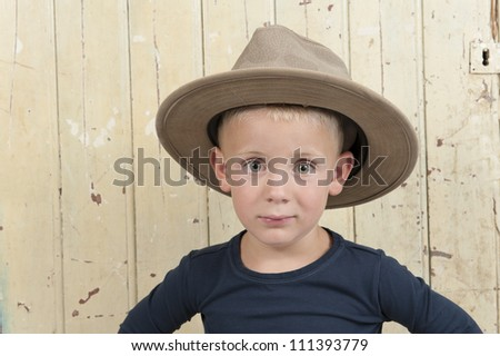little boy with cowboy hat against an old wooden door - stock photo