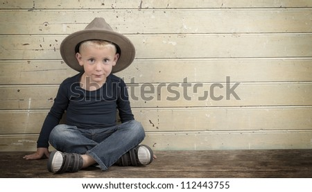 little boy with cowboy hat seated against an old wooden door - stock photo